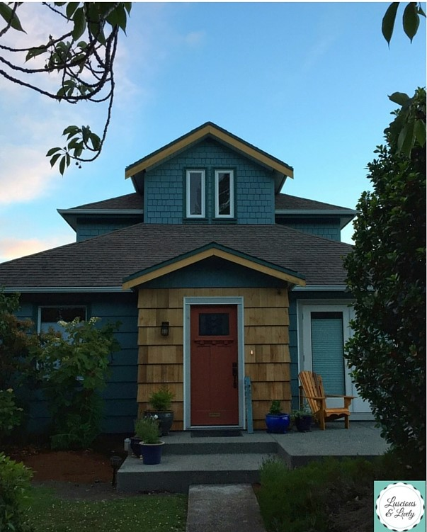House with teal siding, cedar shake details and a red door