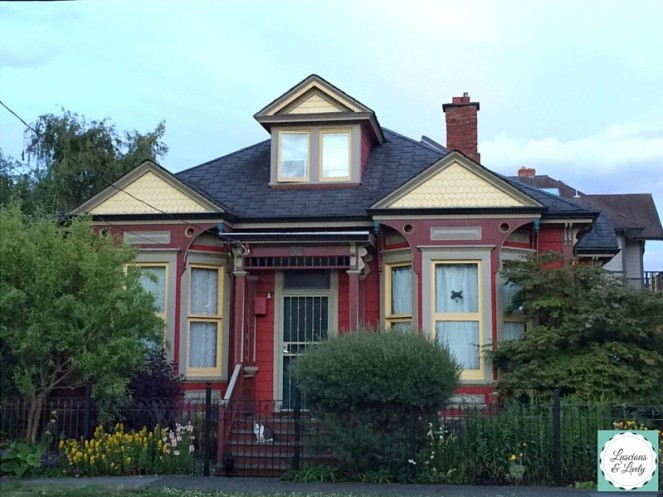 red and yellow house with double bay windows. A black cat and a calico cat sit outside.